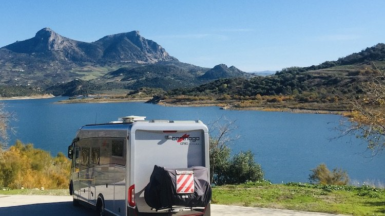 A parked motorhome overlooking a blue lake and mountains in Spain