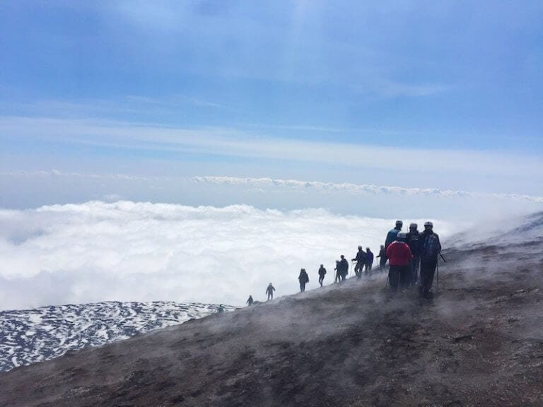 Climing Mount Etna in Sicily, above the clouds with a clear blue sky