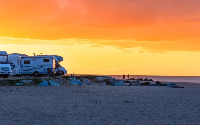 Motorhomes by the beach at sunset