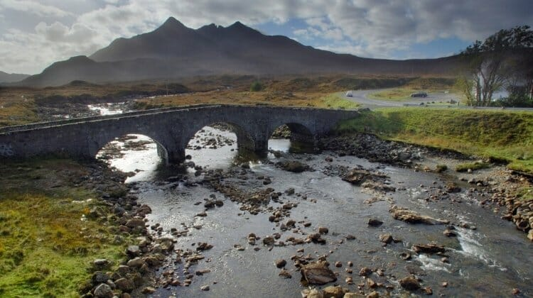 Ancient three arched bridge over a river on Skye