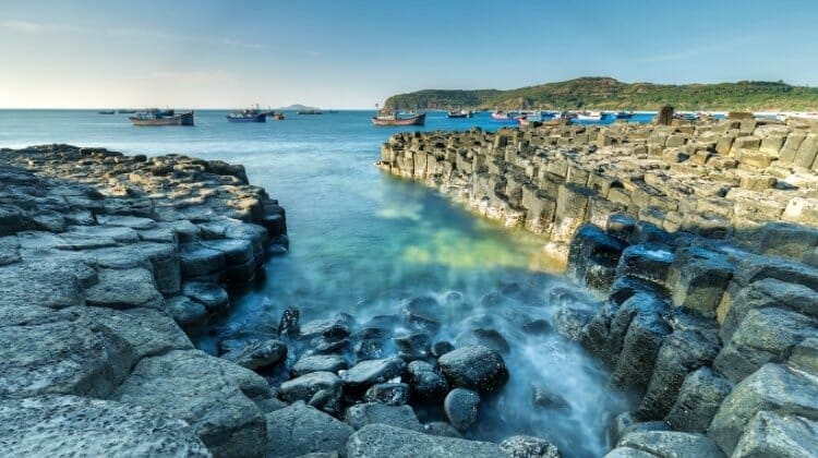 The Giants Causeway with blue seas and fishing boats