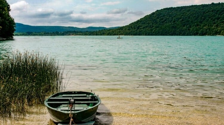 Pale turquoise lke with wooded hills and green fishing boat