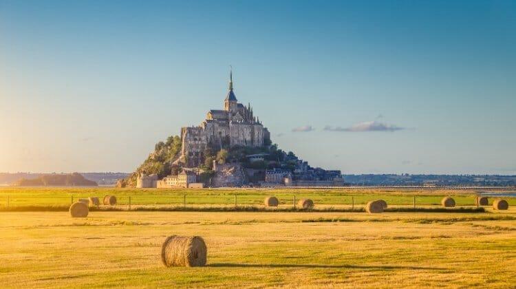 Mont Saint-Michel seen across a golden field of wheat with a blue sky