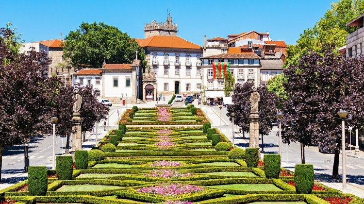 Lush green gardens of Guimaraes, with the red rooved historic town in the background