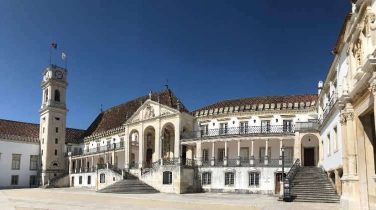 The ornate buildings of Coimbra University around a central square of pale stone