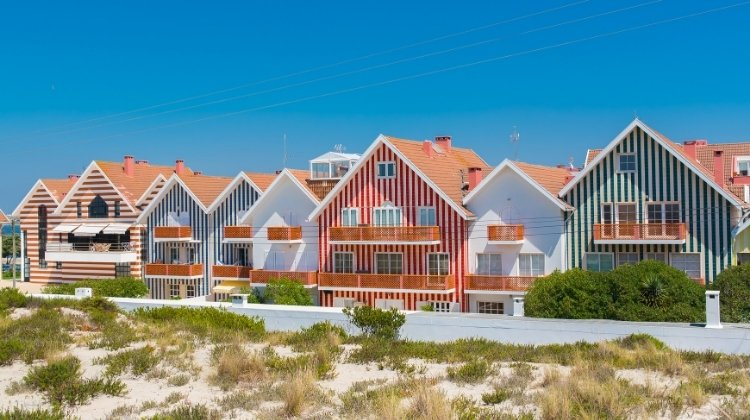 red, blue and white striped houses with small sand dunes in front