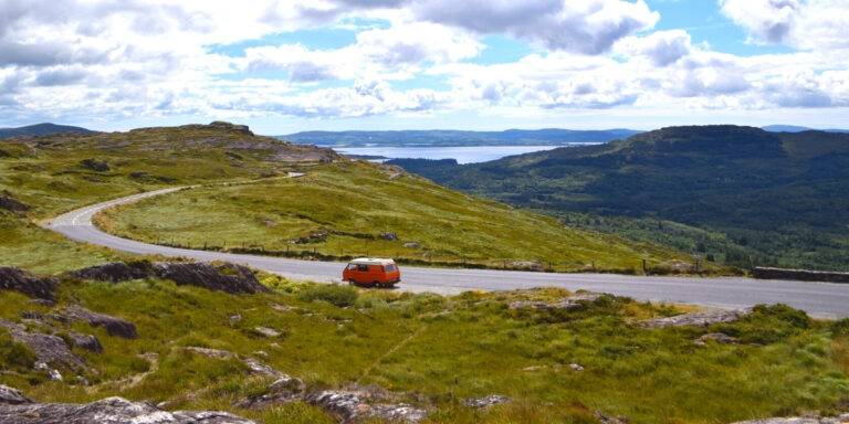 red campervan on a road with Irish mountains in the background