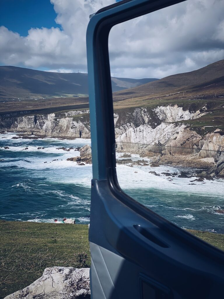 View of dramatic white cliffs and green fields through a campervan window